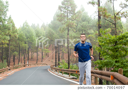 Young man exercising on the road with autumn landscape background 70014097