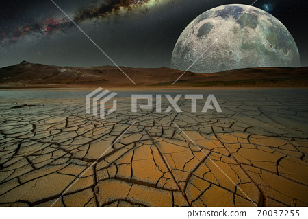 Fantastic night landscape with cracked earth  mountains and moon. Elements of this image furnished by NASA. 70037255