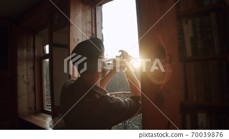 Russia, Moscow - Man at home in quarantine plays music from the windows - flash mob during pandemic of n-cov19 Coronavirus 70039876