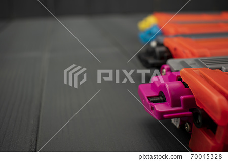 Toner cartridges in magenta, black, cyan and yellow colors on gray wooden background 70045328