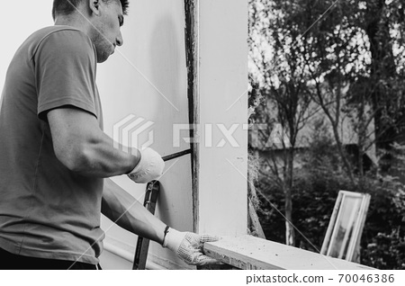 the master dismantles the old window with a crowbar, weighs the old window frame from the wall with a crowbar, performs dismantling work. 70046386