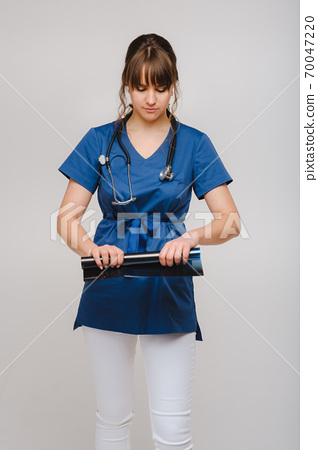 Female Brunette Doctor Looking at Tomography X-ray Film 70047220