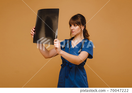 Female Brunette Doctor Looking at Tomography X-ray Film 70047222