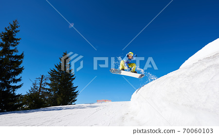 Snowboarder at jump inhigh mountains at sunny day. 70060103