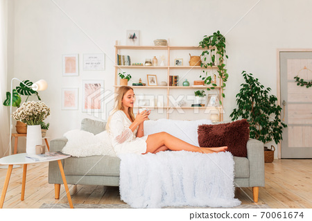 Young beautiful girl having cup of coffee on a couch. Miracle relaxed morning concept 70061674