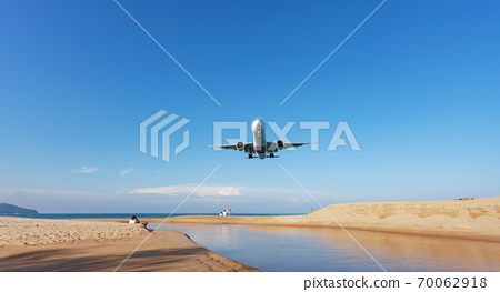 Commercial airplane landing above sea in summer season and clear blue sky over beautiful scenery nature background,concept business travel and transportation background. 70062918