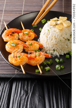 Garlicky and buttery, this simple Japanese Garlic Fried Rice topped with garlic chips with fried shrimps close-up in a plate. Vertical 70064992