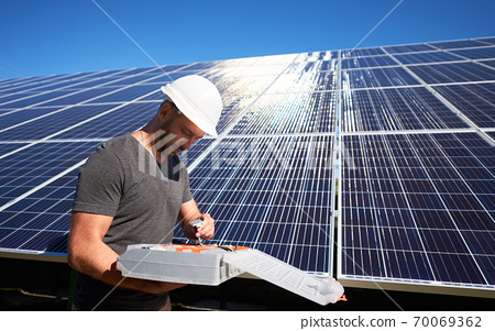 Concentrated architect keeping equipment standing near solar panels. 70069362