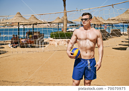 Handsome fit strong athletic young man in swimming trunks holds a volleyball ball on a beach sand volleyball court with net in a sea resort. Fitness model or sportsman on vacation. 70070975