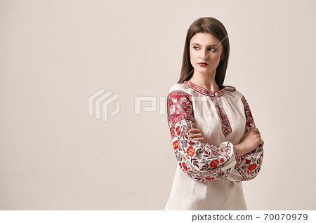 Young beautiful brunette girl wearing gorgeous ethnic style embroidered shirt, modern derivative from traditional Ukrainian vyshyvanka design. Fashion model in studio. 70070979