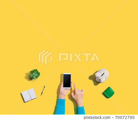 Person using smartphone with piggy bank 70072780