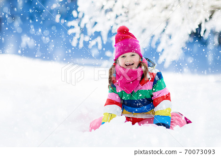 Child playing with snow in winter. Kids outdoors. 70073093