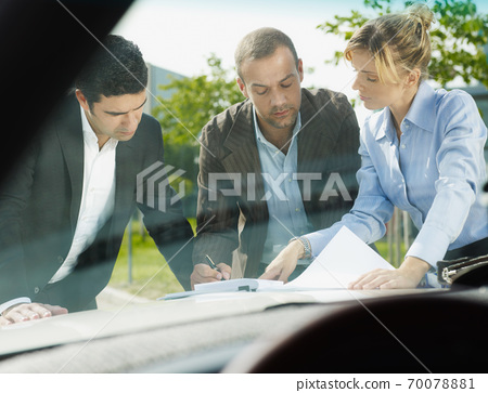 Team Of Business People Signing Contract On Car Hood 70078881