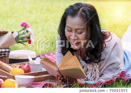 Elderly lifestyle concept. Senior women 50s reading attractive book in her hand 70081955