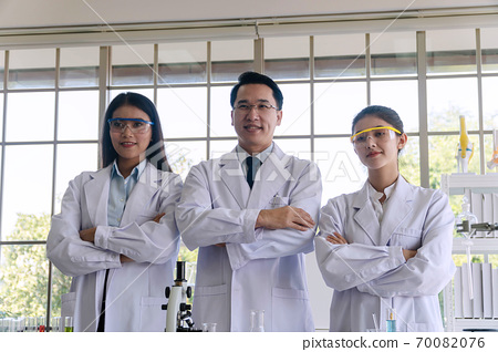 Teams of researchers standing arms crossed together in the laboratory. 70082076