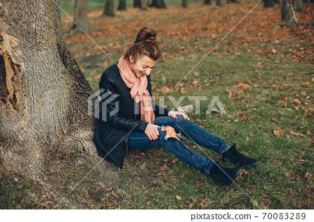 Girl with a broken leg in the autumn park 70083289