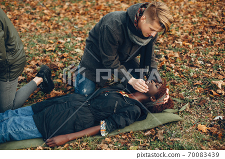 Two boys in a autumn park help a african girl 70083439