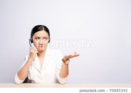 Woman operator in headset feel angry over white background 70085342