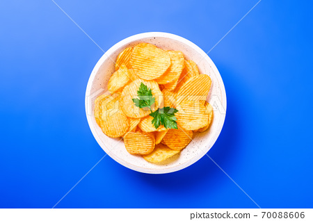 Fried corrugated golden potato chips with parsley leaf in wooden bowl on blue background, top view 70088606