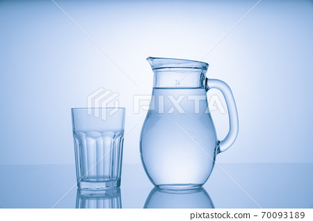 Pitcher with drinking water and a glass with a drink, blue tone 70093189