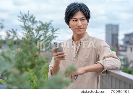 一個年輕人在建築物的屋頂上一隻手抽著智能手機的電子煙 70096402