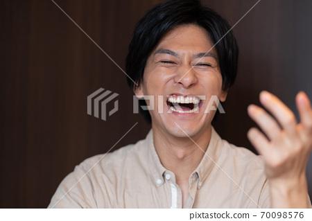 폭소하는 젊은 남자의 얼굴의 업 70098576