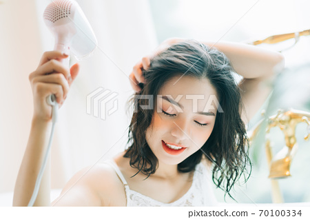 the woman is drying her hair 70100334
