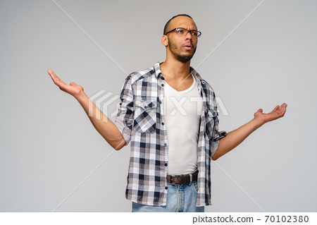 I don't know gesture - Young afrcian american man over grey background being at a loss, showing helpless gesture with arm and hands, as if he does not know what to do 70102380