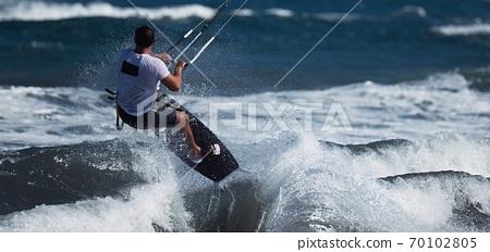 Athletic man jump on kite surf board on a sea waves 70102805
