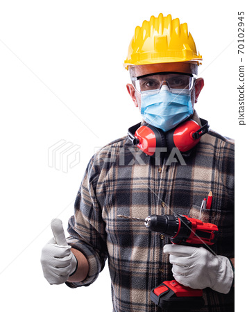 Carpenter at work protects the face with the surgical mask. Carpentry. Covid-19 prevention. 70102945