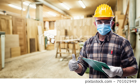 Carpenter at work protects the face with the surgical mask. Carpentry. Covid-19 prevention. 70102949