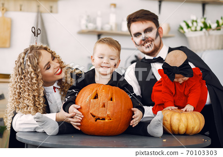 Family in costumes getting ready for halloween at home 70103303
