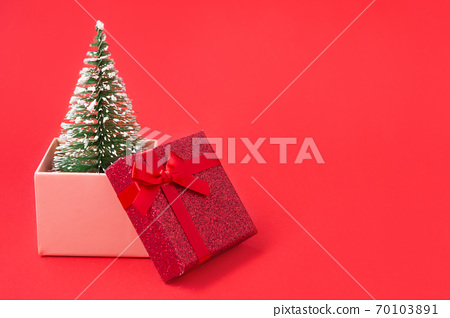Christmas tree sticks out of an ajar gift box, Christmas concept and gifts 70103891