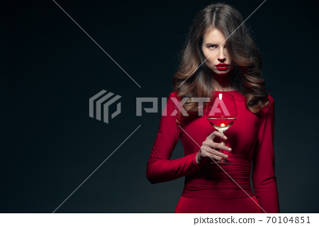 Woman with bright makeup, hairstyle wearing red dress posing with glass of vine over dark background, isolate 70104851