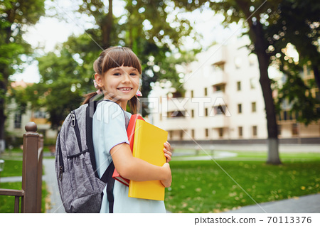 Happy little student girl with a backpack on her way to school. 70113376