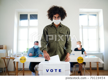 Young man putting his vote in the ballot box, elections and coronavirus. 70119454