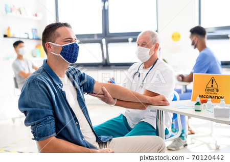 Man with face mask getting vaccinated, coronavirus, covid-19 and vaccination concept. 70120442
