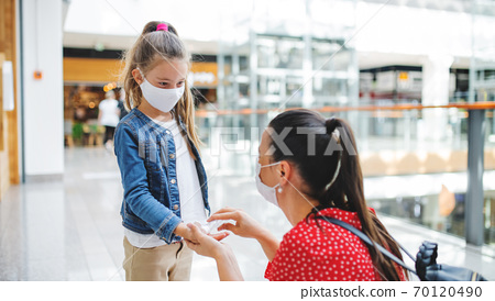 Mother and daughter with face mask disinfecting hands indoors in shopping center, coronavirus concept. 70120490