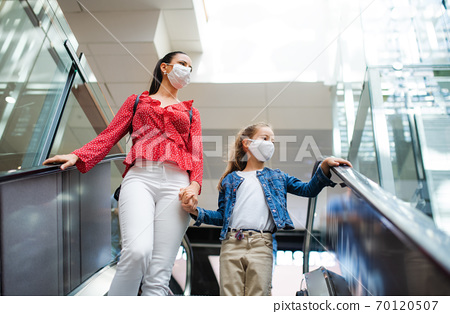 Mother and daughter with face mask on escalator indoors in shopping center, coronavirus concept. 70120507