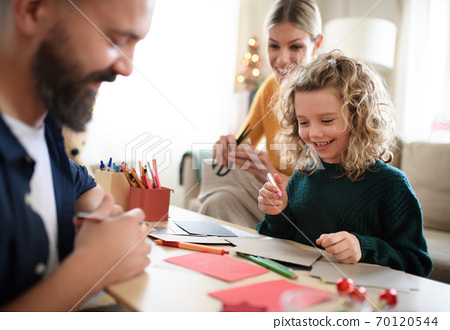 Family with small daughter indoors at home at Christmas, making Christmas cards. 70120544