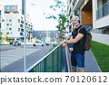 Portrait of mature man with skateboard outdoors in city, going back to work. 70120612