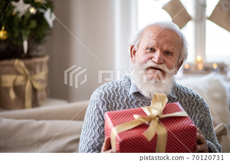 Front view of happy senior man with present box indoors at home at Christmas. 70120731
