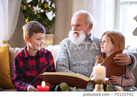 Small children with senior grandfather indoors at home at Christmas, looking at photographs. 70120742