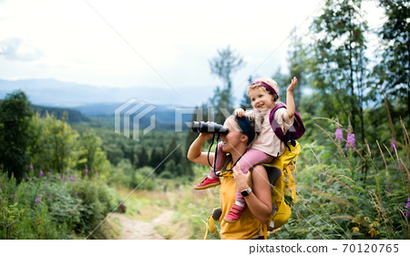 Mother with small toddler daughter hiking outdoors in summer nature, using binoculars. 70120765