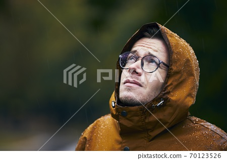 Man in waterproof jacket during rain 70123526