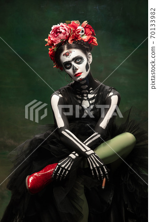 Young girl in the image of Santa Muerte, Saint death or Sugar skull with bright make-up. Portrait isolated on studio background. 70133982