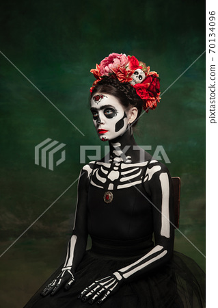 Young girl in the image of Santa Muerte, Saint death or Sugar skull with bright make-up. Portrait isolated on studio background. 70134096