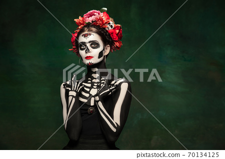 Young girl in the image of Santa Muerte, Saint death or Sugar skull with bright make-up. Portrait isolated on studio background. 70134125