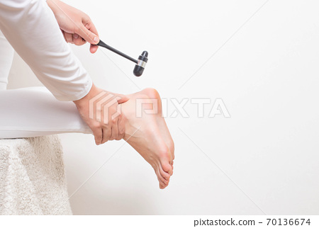 A neurologist doctor checks the Achilles reflex with a neurological hammer. Checking the tibial nerve and the presence of an intervertebral hernia of the spine, copy space 70136674