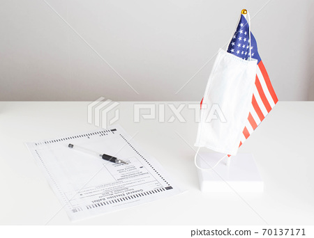 Presidential election in the United States during coronavirus pandemic COVID 19. Protective medical mask is put on the USA flag. Paper ballot is on the table. Choice between candidates for president 70137171